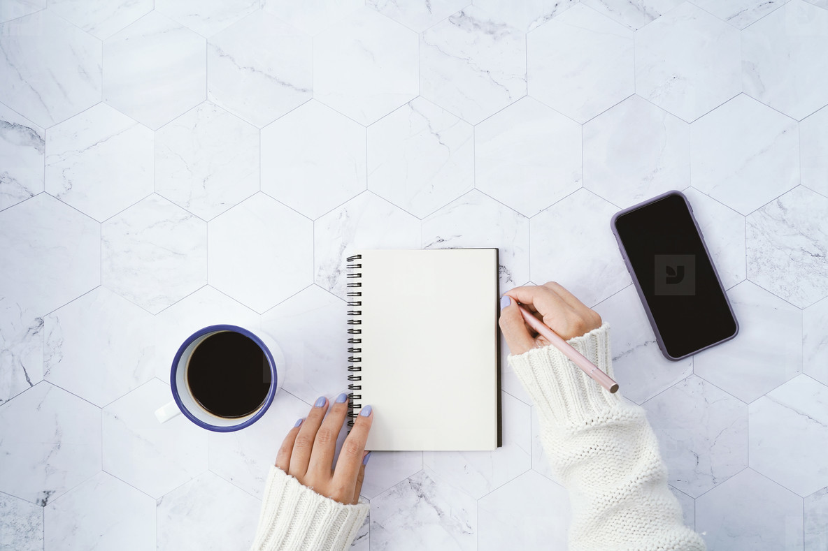 Flat lay of woman writing on blank notebook
