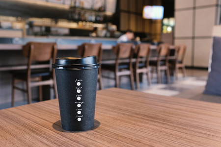 Take away coffee cup on wooden table in modern cafe