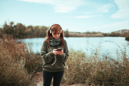 Young woman using her smartphone near a lake with headphones