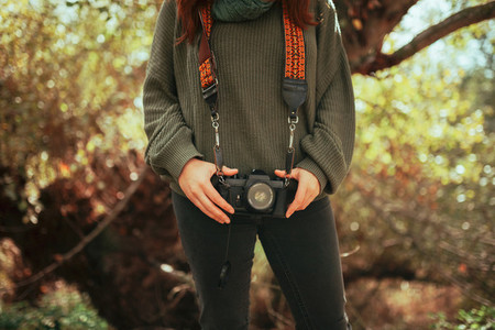 Young woman closeup with old film camera in her hip