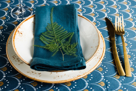 Festive table place for Christmas or New Year family dinner with Winter decor  Golden cutlery  ceramic dishes decorated with plant on a napkin