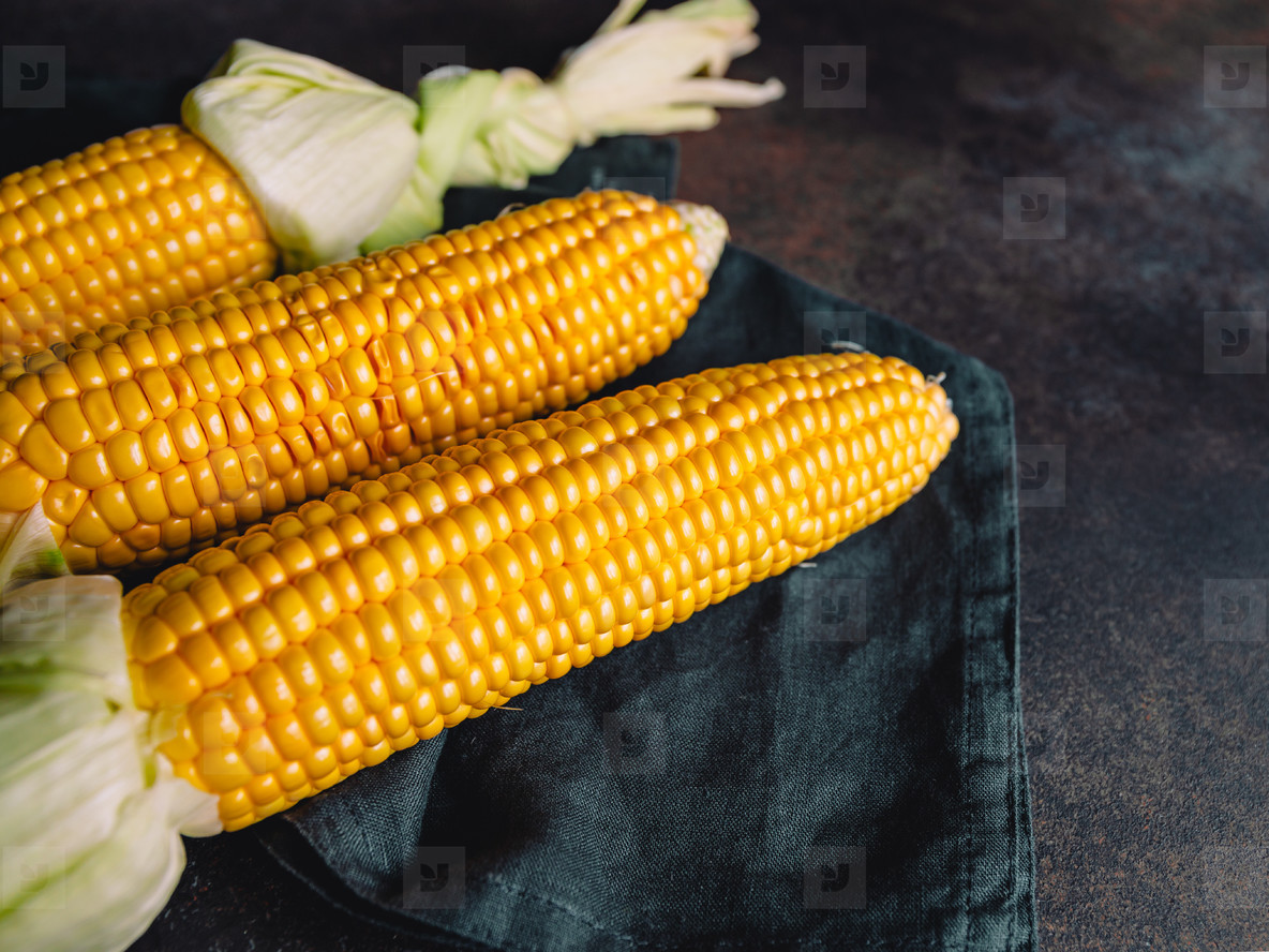 Fresh corn cobs on a table  The concept of preparation healthy veggie food