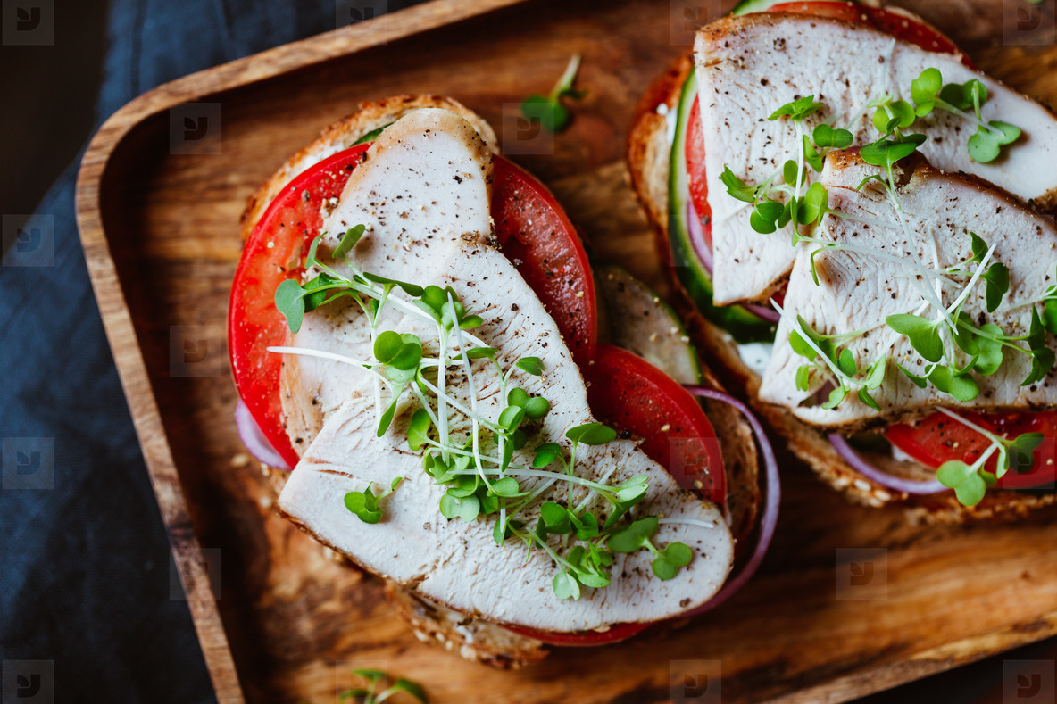 Sandwiches with turkey meat and fresh vegetables served with microgreens on a wooden plate  Top view  flat lay  macro food photography