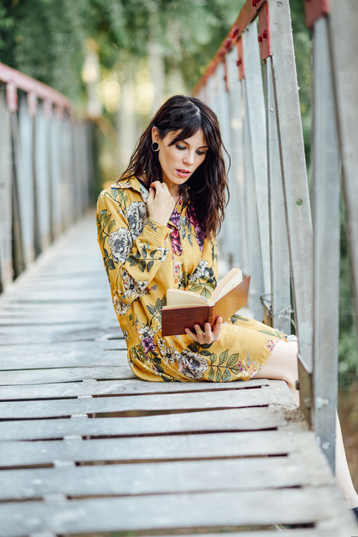 Young woman reading a book on a rural bridge