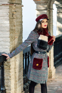 Young beautiful girl with very long hair looking away wearing winter coat and cap outdoors