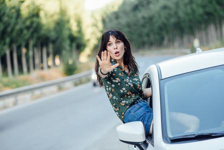 Woman peeking her body through the window of the car