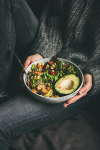 Woman holding bowl with fresh salad  avocado  beans and vegetables