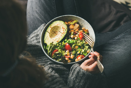 Woman holding bowl with healthy vegetarian dinner  top view