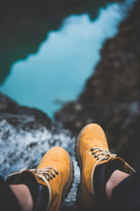 Feet of nature explorer in boots sitting over river canyon