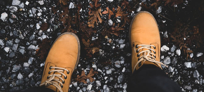 Feet of traveler in boots standing on ground  wide composition