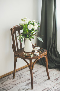 Spring white buttercup flowers in enamel jug on vintage chair