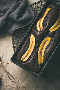 Chocolate banana cake with cinnamon in baking tin  vertical composition