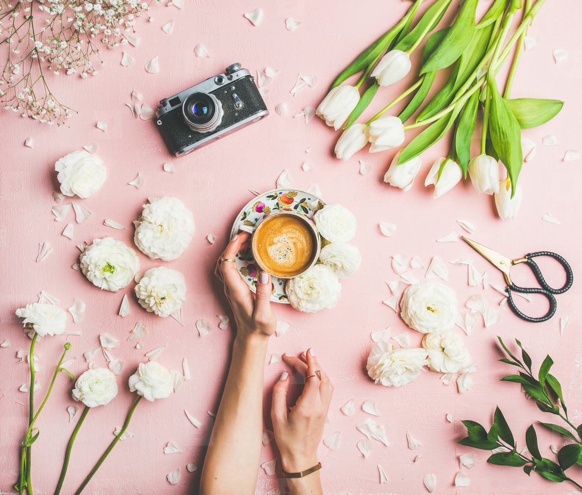 Female hands holding coffee  fresh flowers and film camera