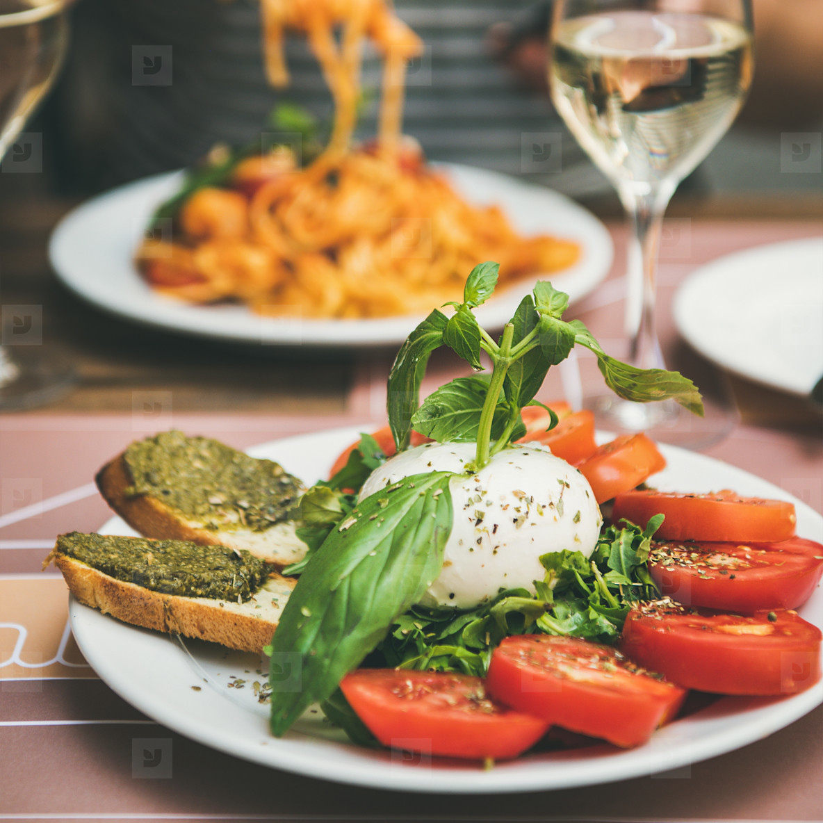 Italian dinner at bistrot with caprese and pasta  square crop