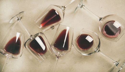 Flat lay of red wine in glasses over grey concrete background