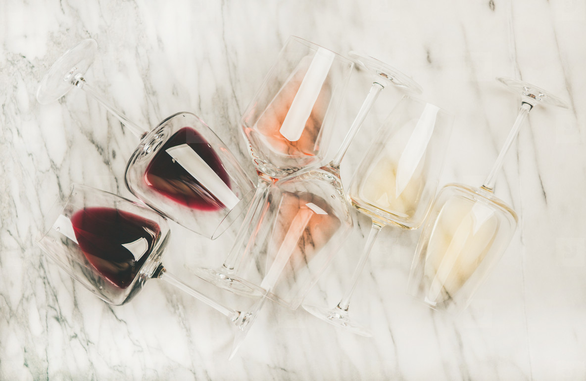 Flat lay of red  rose and white wine in glasses