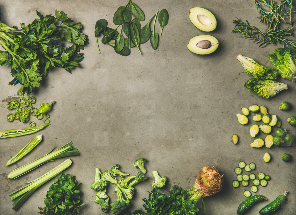 Flat lay of whole and cut green vegetables and herbs
