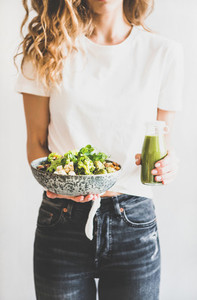 Woman holding vegan superbowl and green smoothie in hands
