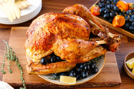 Roasted whole turkey on a table with fruits for family Christmas or Thanksgiving Holiday