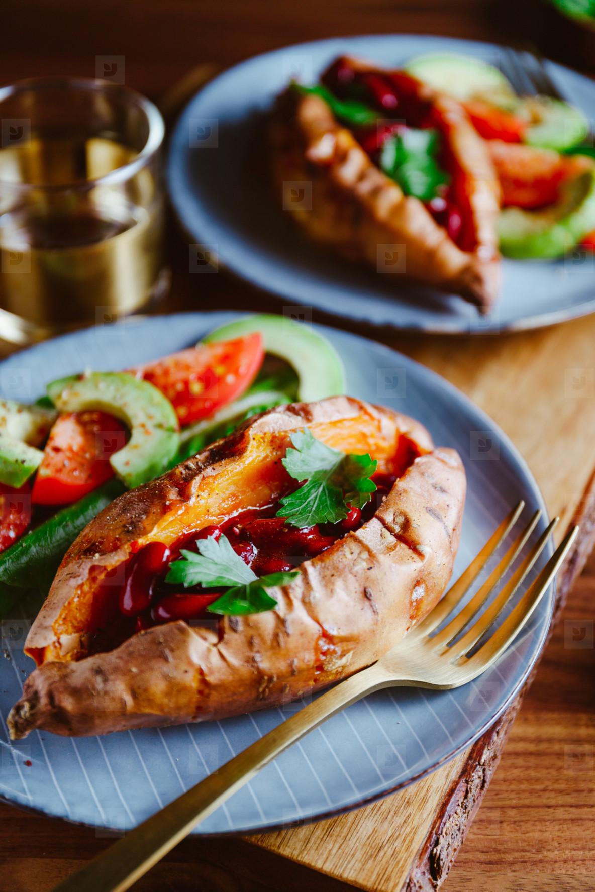 Baked sweet potato filled with red beans stewed in tomato paste served with avocado and cherry tomatoes on a plate  Healthy veggie recipe