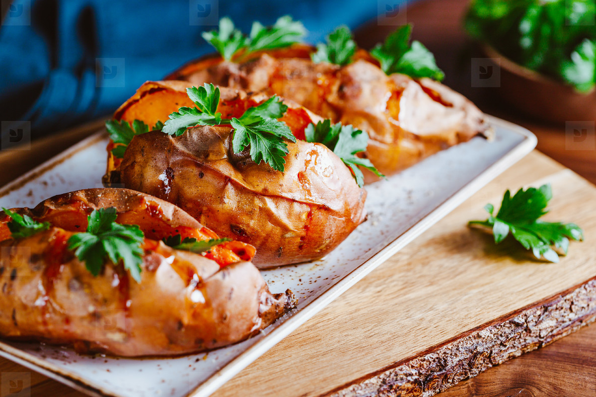 Baked three sweet potatoes with fresh parsley on a white ceramic dish  Healthy veggie dinner or lunch