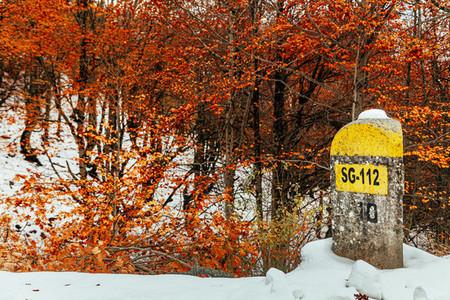 Road milestone in a snowy mountain road in spain