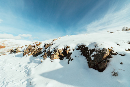 Snow covered rocks on the mountain with blue sky