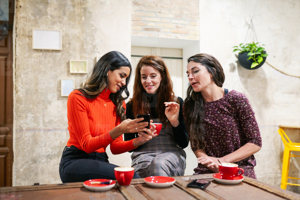 Group of three happy friends drinking coffee in a cafe bar