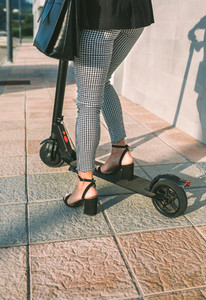 Unrecognizable businesswoman legs with e scooter outdoors