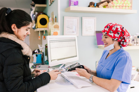 Young woman paying in a veterinary with credit card