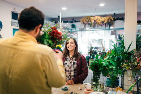 Young woman buying a bouquet of flowers in a florist
