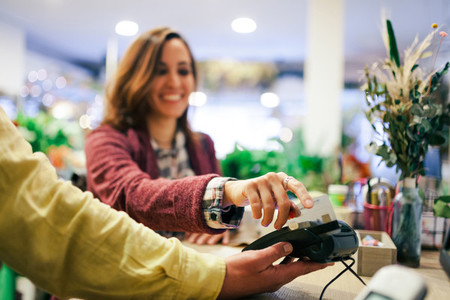 Young woman paying in a veterinary with a credit card