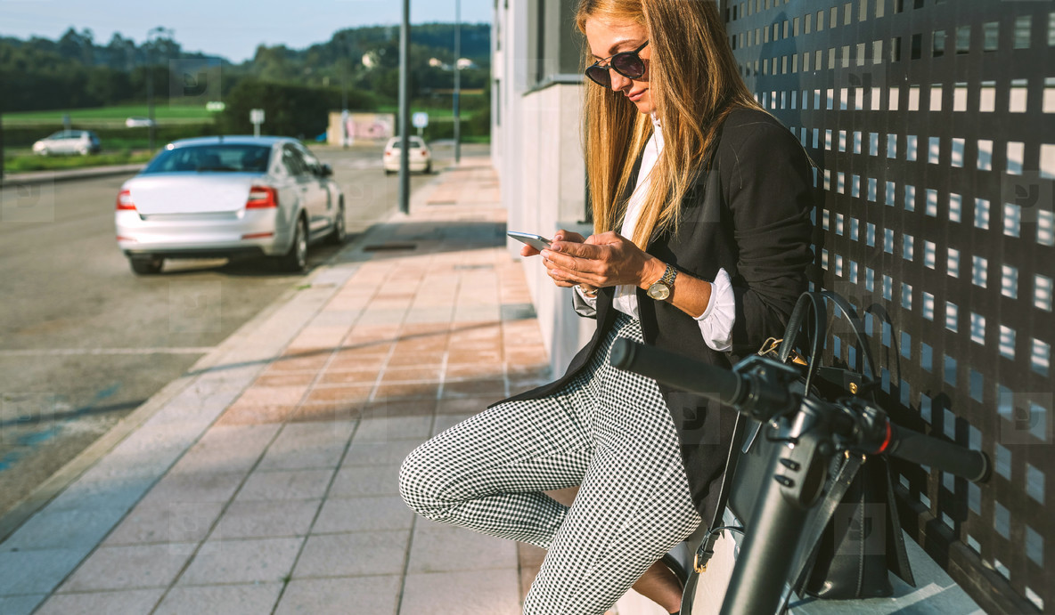 Businesswoman with mobile and her scooter next