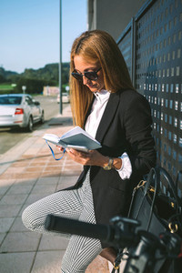 Businesswoman reading diary with her scooter next
