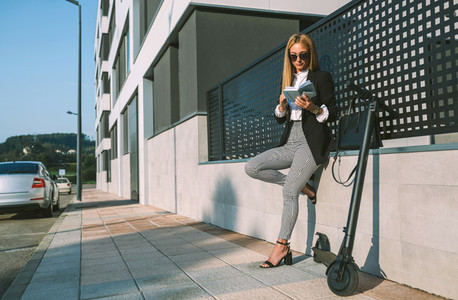 Businesswoman reading notebook with her scooter next