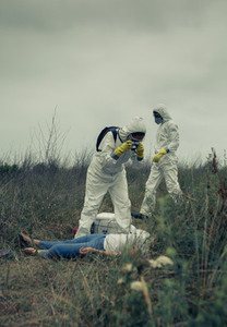 Man and woman in bacteriological protective suit taking a photo of a corpse