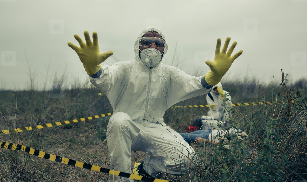 Man with bacteriological protective suit prohibiting entering cordoned off area