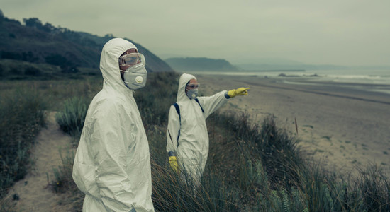 People in bacteriological protective suits watching the sea