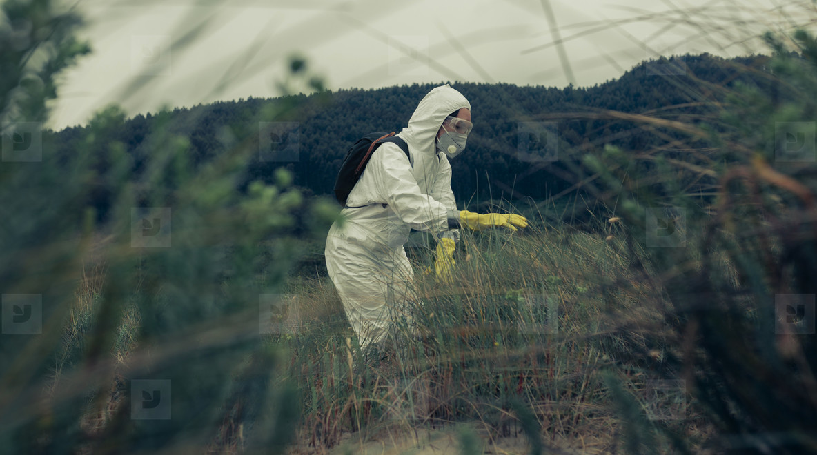 Woman in protective suit searching among the vegetation