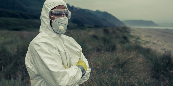 Man in bacteriological protective suit watching the sea