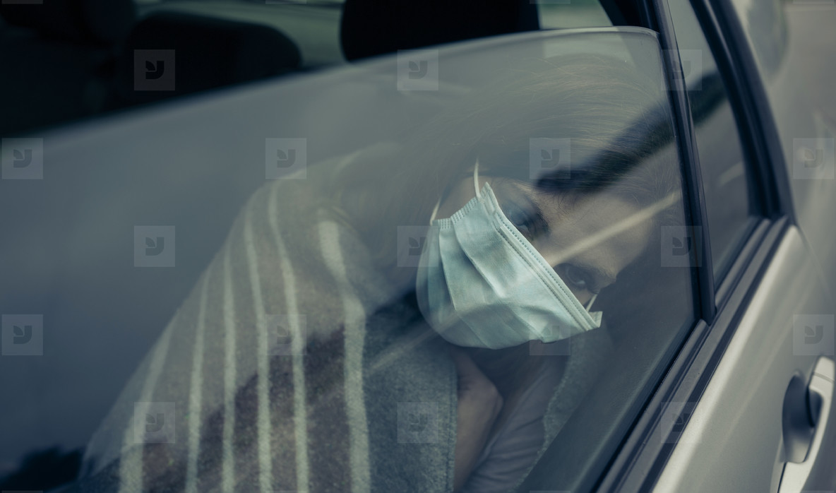 View through the car window of a woman with mask