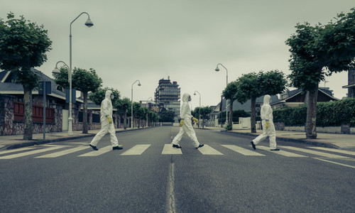 People with bacteriological protection suits in a crosswalk