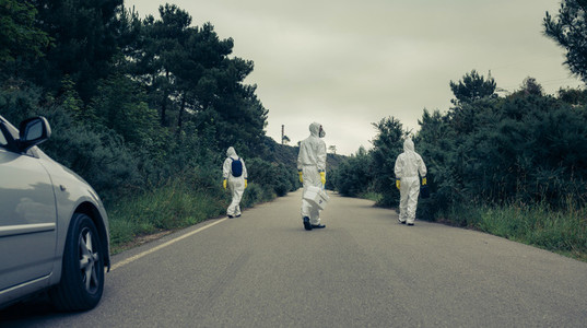 People with bacteriological protection suits walking