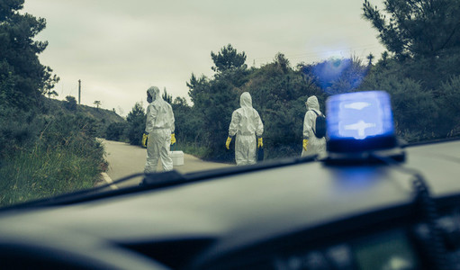 View from emergency car of people with bacteriological protection suits