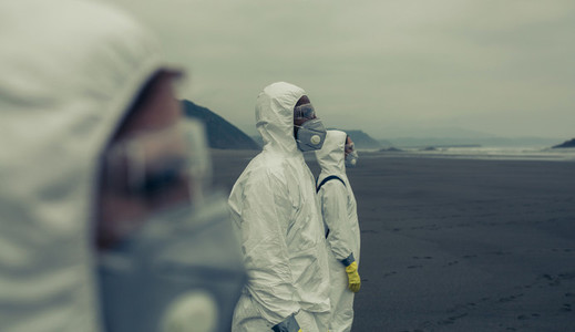 People with bacteriological protection suits looking at the sea
