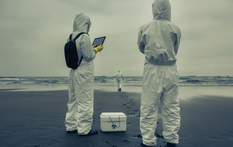 People with bacteriological protection suits looking for evidence at sea