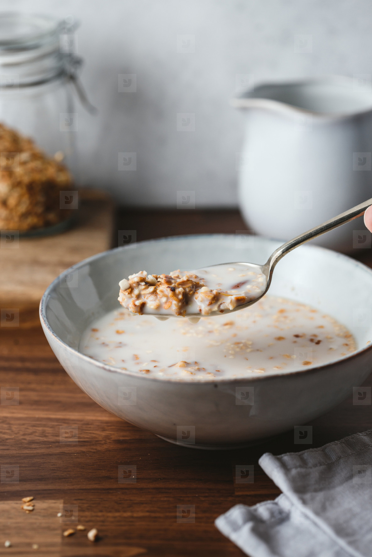 Hand holds a spoon with baked granola and almond milk  Healthy vegetarian breakfast