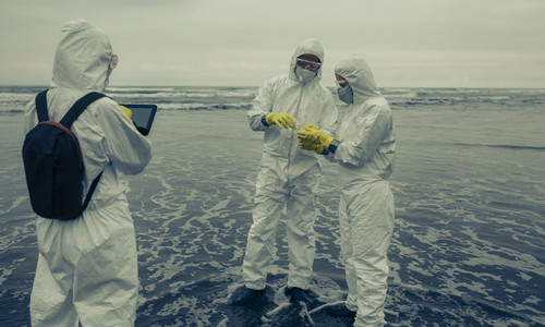 People with protection suits analyzing seawater