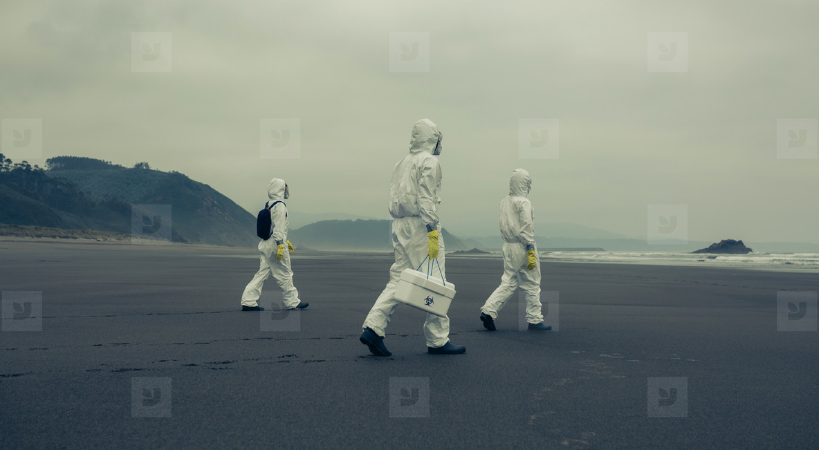 People with bacteriological protection suits walking on the beach