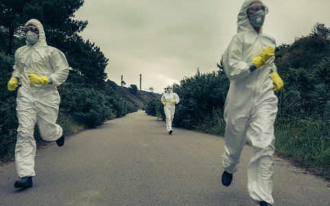 People with bacteriological protection suits running